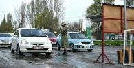 Сотрудник МВД проверяет документы на контрольно-санитарном пункте в городе Бишкек, где введено режим ЧС в связи с распространением коронавируса