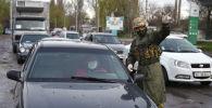Сотрудник МВД проверяет документы на контрольно-санитарном пункте в городе Бишкек