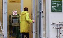 Прохожая около входа в офис банка. Архивное фото