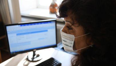 Женщина в медицинской маске за копьютером. Архивное фото