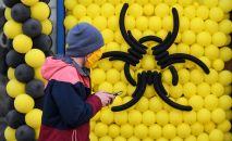 Молодой человек в защитной маске проходит мимо знака Опасность. Архивное фото