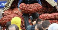 Мужчина выгружает мешок картофеля. Архивное фото