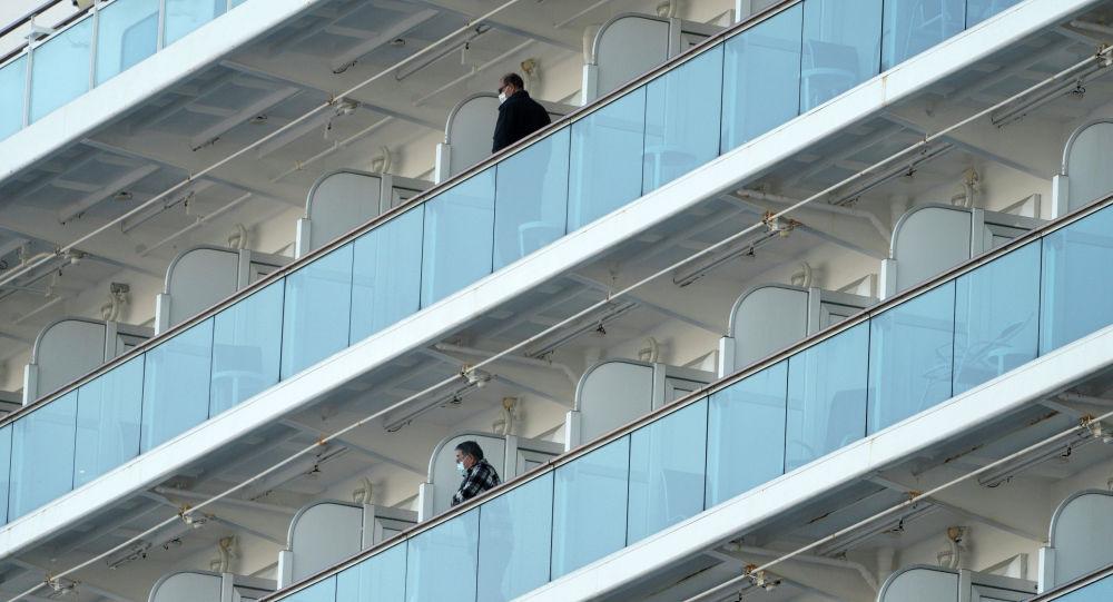Пассажиры стоят на балконе круизного лайнера Diamond Princess, стоящего на якоре у порта Иокогама недалеко от Токио. Архивное фото