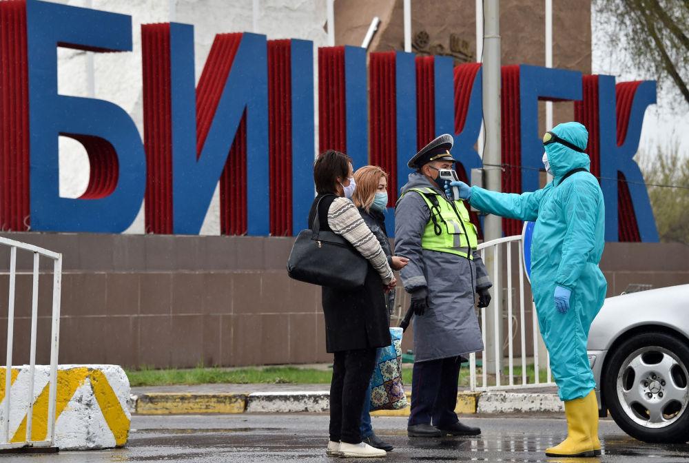Медицинский работник проверят температуру прохожих на контрольно-пропускном пункте на въезде в Бишкек. 1 апреля 2020 года