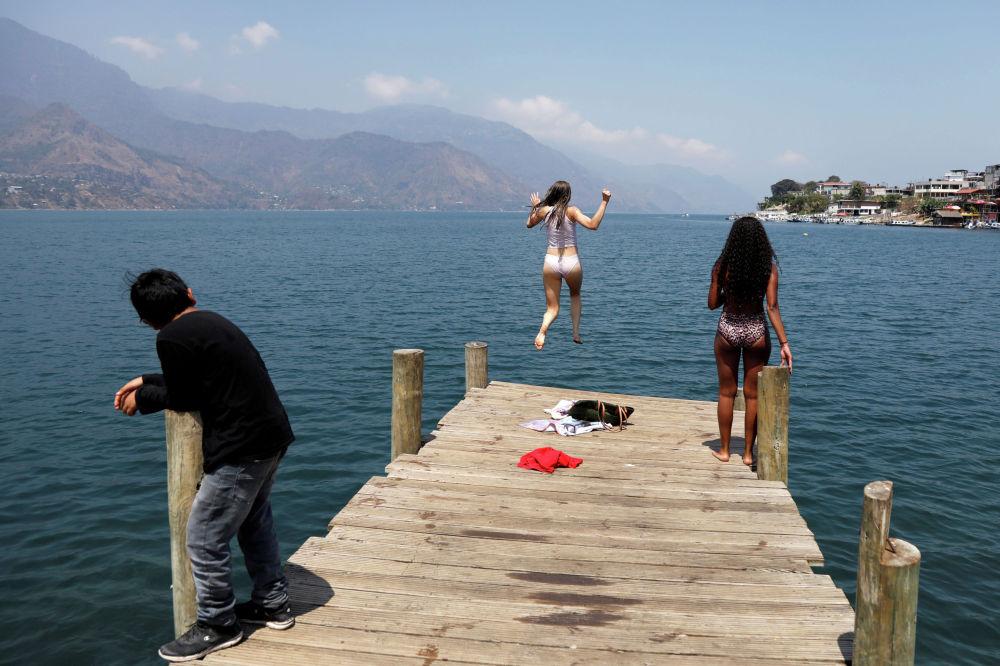 Туристы прыгают с пирса в Гватемале. 27 марта 2020 года