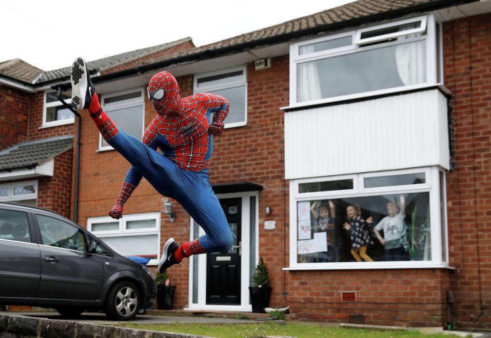 Мужчина в костюме человека-паука развлекает детей во время карантина в Стокпорте (Великобритания)