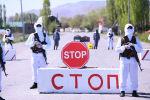 Сотрудники правоохранительных органов стоят на блок-посту в одном из населенных пунктов Ошской области. Архивное фото