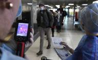 Медицинские сотрудники измеряют температуру прибывших пассажиров с помощью тепловизора. Архивное фото