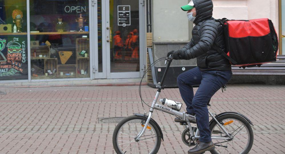 Курьер по доставке еды едет на велосипеде. Архивное фото