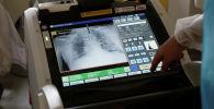 Сотрудник медицинского персонала делает рентген легких пациенту. Архивное фото