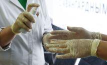 Медкызматкерлер колун дезинфекция кылууда. Архивдик сүрөт