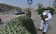 Военнослужащие Национальной гвардии и сотрудники патрульной милиции в лицевых масках на контрольно-пропускном пункте на окраине Бишкека. 26 марта 2020 года