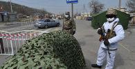 Военнослужащие Национальной гвардии и сотрудники патрульной милиции в лицевых масках на контрольно-пропускном пункте на окраине Бишкека. Архивное фото