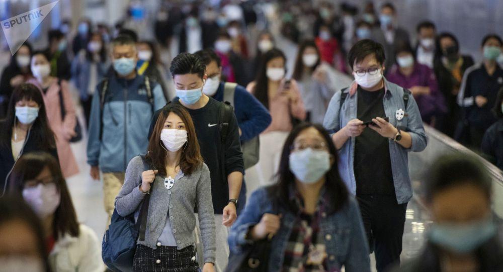 Люди в медицинских масках на переходе одной из станций метро в Гонконге. Архивное фото