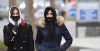 Девушки в медицинских масках на одной из улиц. Архивное фото