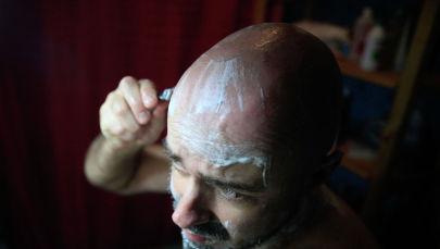 Мужчина бреет голову. Архивное фото