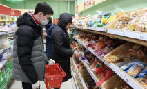 Супермаркетте нан тандап жаткан кардарлар. Архив