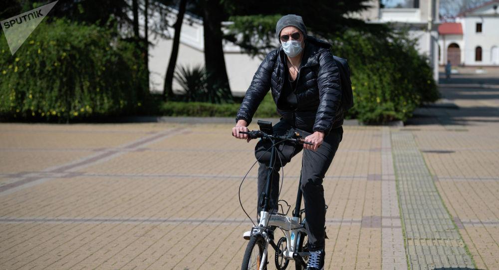 Молодой человек в защитной маске на велосипеде в городе