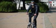 Молодой человек в защитной маске на велосипеде в Сочи.