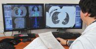 Дарыгер компьютердик томографиянын натыйжаларын карап отурат. Архив