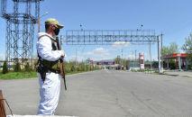 Сотрудник правоохранительных органов с оружием стоит на блокпосту в одном из населенных пунктов Ошской области
