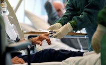 Медицинский персонал в защитном костюме лечит пациента, страдающего коронавирусной болезнью (COVID-19). Архивное фото