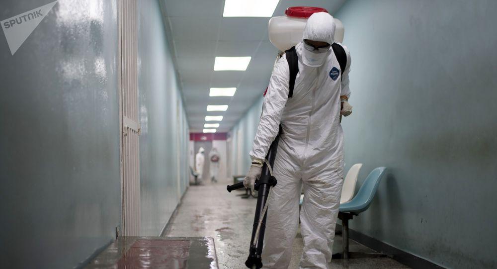 Сотрудник дезинфекционной бригады гражданской защиты проводит обработку поверхностей дезинфицирующим раствором в общей больнице