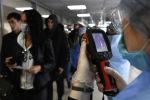 Медицинские сотрудники контролируют прибывающих пассажиров в аэропорту. Архивное фото