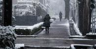 Люди идут по тротуру во время снегопада в Бишкеке. Архивное фото
