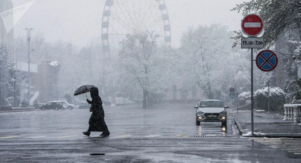Люди с зонтами переходят дорогу на Старой площади в Бишкеке. Архивное фото