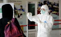 Медицинский сотрудник в защитном костюме проверяет возвращающегося пассажира в аэропорту. Архивное фото