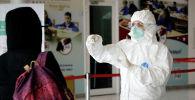 Медициналык кызматкер коопсуз костюмчан кишинин температурасын тепловизор менен текшерип жатат. Архив
