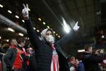 Фанат футбольной команды в защитной маске на стадионе перед матчем