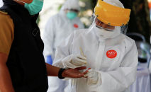 Медицинский работник в защитном снаряжении берет образец крови, чтобы проверить человека на наличие коронавирусной болезни (COVID-19). Архивное фото