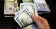 Женщина считает банкноты в долларах США. Архивное фото