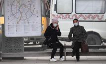 Женщины в медицинских масках на автобусной остановке в Москве. Архивное фото