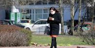 Жительница города идет по улице в защитной маске. Архивное фото