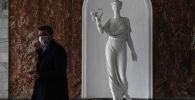 Мужчина в медицинской маске проходит мимо статуи. Архивное фото