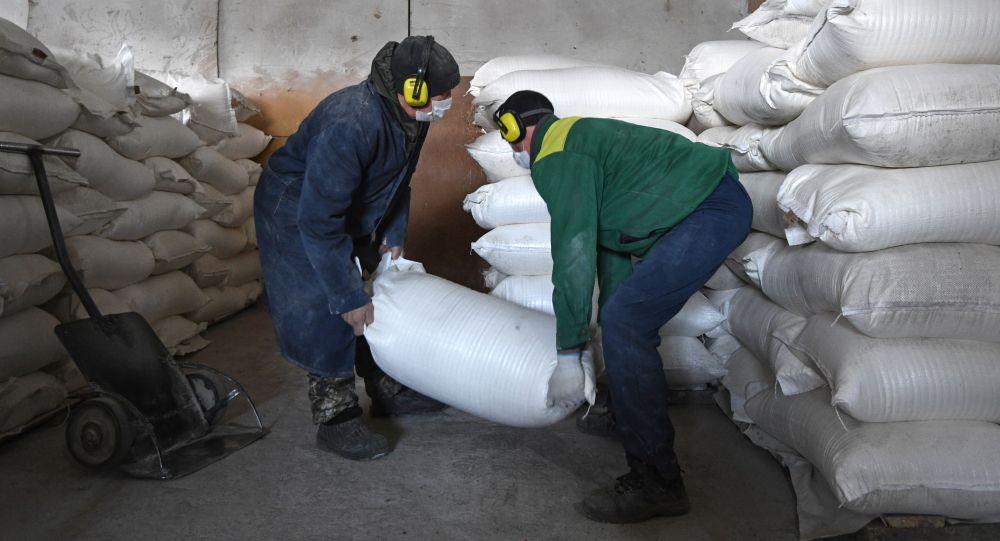Рабочие укладывают мешки с мукой на складе готовой продукции