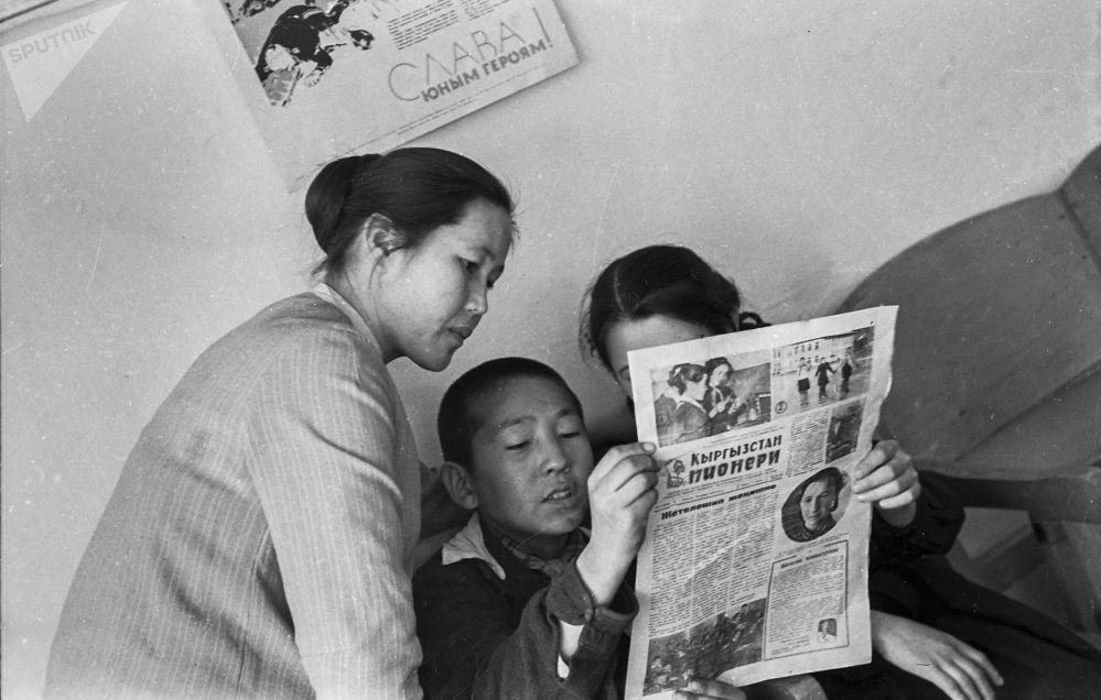 Мугалим менен окуучулар Кыргызстан пионери гезитин окуп жатат