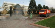 Муниципальный работник моет пустую улицу возле дома правительства после того, как власти объявили чрезвычайное положение в Бишкеке и ввели комендантский час в качестве дополнительной меры для предотвращения распространения коронавирусной болезни (COVID-19) в Бишкеке. Кыргызстан, 26 марта 2020 года