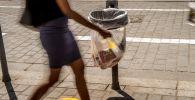 Девушка бросает мусор в урну. Архивное фото