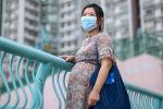 Беременная женщина в медицинской маске. Архивное фото
