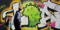 Мужчина смотрит на граффити на стене во время вспышки коронавирусной болезни (COVID-19) в Вене. Архивное фото