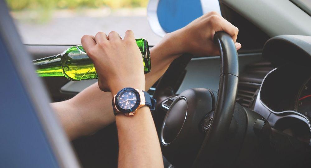 Водитель пьет алкогольный напиток за рулем. Иллюстративное фото