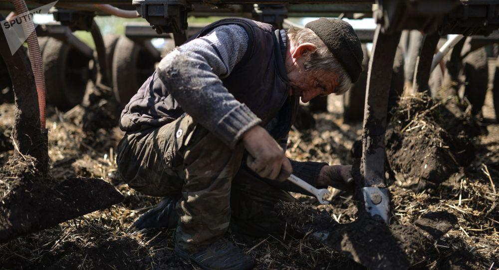 Механизаторы во время ремонта трактора. Архивное фото