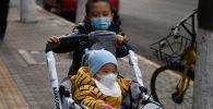 Пекиндин көчөсүндө бараткан кичинекей балдар. Архивдик сүрөт