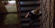 Женщина спускается по лестничной клетке в жилом доме. Архивное фото