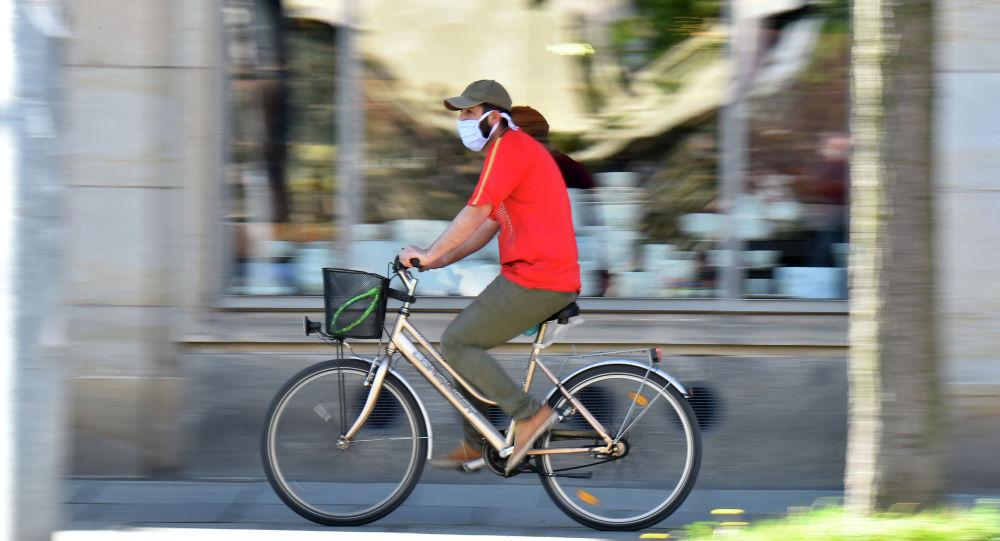 Человек одетый в защитную маску едет на велосипеде. Архивное фото