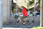 Коопсуз бет кап кийген киши велосипед тээп баратат. Архив